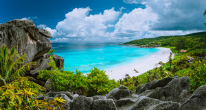 Picturesque panoramic shot of Grand Anse, La Digue island, Seychelles. Huge granite rock formation, bright white sand tropical beach with turquoise blue crystal clean water and cloudscape