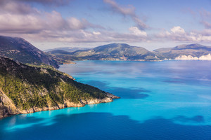 Picturesque rocky coastline on Kefalonia island. Amazing watercolor landscape in sunset light with cloudscape