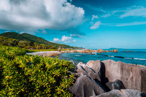 Picturesque tropical coastline with hidden beach with unique big granite rocks, lush foliage and some clouds, Grand L Anse, La Digue, Seychelles