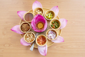 pink lotus petal flower decorated and is part of thai snack food on clear wood table