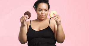 Plus size model in studio shoot happy smiling and eats a donut