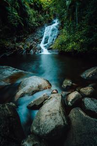 Port Glaud Waterfall on Mahe island, Seychelles. Beautiful rocks in foreground.