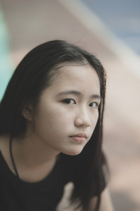 portrait headshot of beautiful asian teenager looking with eyes contact outdoor