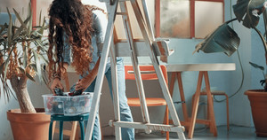 Portrait of a beautiful long-haired female artist at work at her canvas in a studio