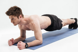 Portrait of a concentrated healthy sportsman doing plank exercise on a fitness mat isolated over white background