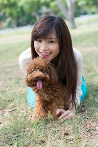 Portrait of a girl and a poodle lying on the grass