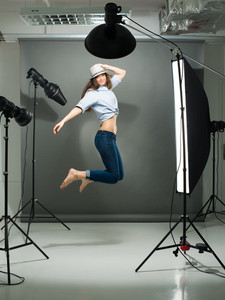 Portrait of a jumping model working in the professional photo studio