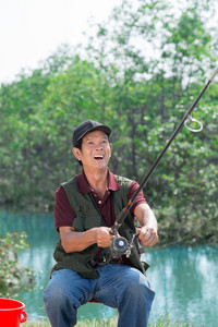 Portrait of a senior excited fisherman catching the fish