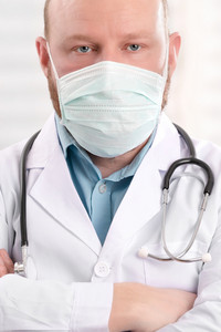 Portrait of a serious doctor wearing surgical face mask and stethoscope