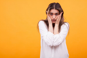 Portrait of a shocked young girl in white shirt over yellow background. Amazed girl