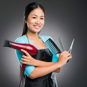 Portrait of a young barber with the equipment for the haircutting against a grey background