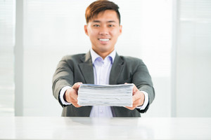 Portrait of a young businessman holding a heap of documents before deadline