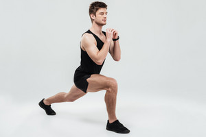 Portrait of a young concentrated man doing squats exercise isolated on a white background