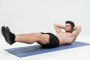 Portrait of a young sportsman doing plank exercise on a fitness mat isolated over white background