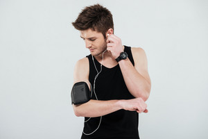 Portrait of a young sportsman with earphones using blank screen mobile phone on armband isolated on a white background