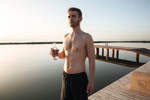 Portrait of a young tired sportsman holding water after jogging outdoors