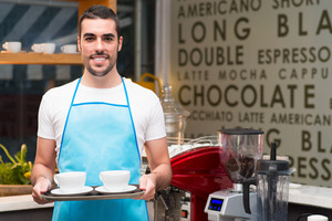 Portrait of a young waiter with cups of coffee in the coffeehouse