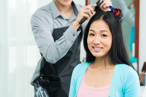 Portrait of a young woman having hair procedure in salon on the foreground