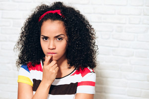 Portrait of angry african american woman looking at camera. Black girl showing jealousy, rage, anger and aggressivity. Upset hispanic wife and domestic life