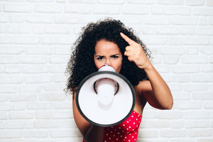 Portrait of angry african american woman shouting with megaphone for protest. Black girl showing rage, anger and rebellion for human rights, strike, pride