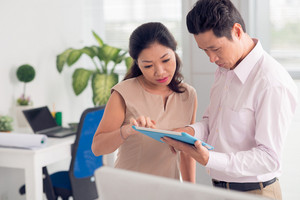 Portrait of Asian business partners using digital tablet in office