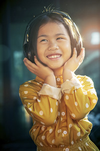 portrait of asian children hearing music in head phone toothy smiling happiness emotion