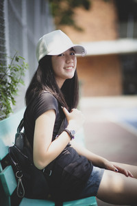 portrait of asian teenager wearing white cap sitting outdoor and  looking with eye contact to camera