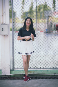portrait of asian teenager wearing white short skirt laughing with happiness emotion