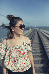 portrait of asian woman happiness emotion toothy smiling face standing on railway track