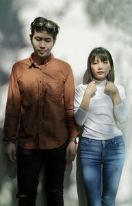 portrait of asian younger man and woman like fashion model standing against beautiful light wall