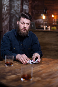 Portrait of attractive bearded man looking at the camera and shuffling cards. Rich man. Attractive man. Stylish beard. Great whisky.