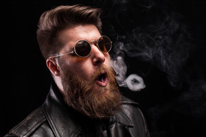 Portrait of bearded hipster man making smoke circles over black background. Dramatic portrait.