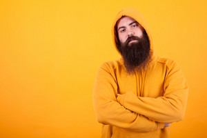 Portrait of Bearded man looking serios at the camera over yellow background. Bad attitude. Stylish man. Long beard.
