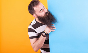 Portrait of bearded man sticking his head out behind a blue pannel over yellow background. Handsome man.