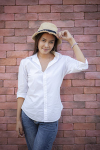 portrait of beautiful asian younger woman with smiling face standing against red brick wall