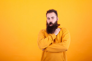 Portrait of beautiful bearded hipster looking amazed over yellow background. Facial expression. Trendy adult. yellow hoodiel.