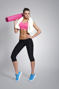 Portrait of beautiful fit woman with exercise mat and towel