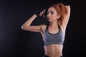 Portrait of beautiful fitness girl during studio photoshoot. Slim powerfull girl.