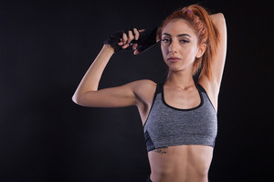 Portrait of beautiful fitness girl during studio photoshoot. Slim powerfull girl.