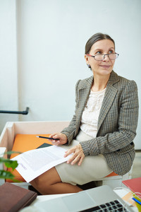 Portrait of beautiful senior entrepreneur in eyeglasses looking away dreamily while sitting in modern office and holding business contract and pen in hands