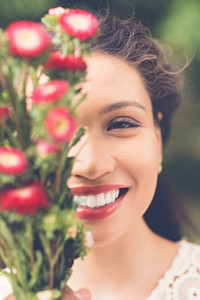 Portrait of beautiful woman holding a bouquet of flowers