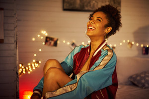Portrait of beautiful young african american woman with afro hair style, sitting on bed at home at night. The girl is laughing for joy and looking up.