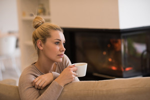 Portrait of beautiful young woman with a mug near a fireplace