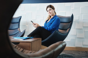 Portrait of business woman holding cell phone at work in office waiting room, sitting on armchair and looking at camera with serious expression. Hispanic lady texting on smartphone.