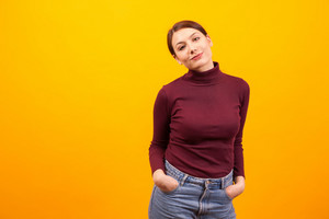 Portrait of caucasian goofy young woman over yellow background. Stylsih young woman. Cheerful girl.