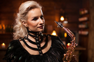 Portrait of caucasian woman singing on her saxophone in a vintage pub. Jazz concert. Performing in a pub.