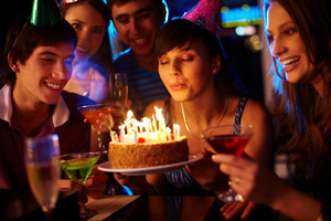 Portrait of charming girl blowing on candles on birthday cake surrounded by friends at party