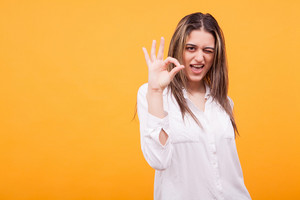 Portrait of charming girl showing ok sign and winking over yellow background. Optimistic girl