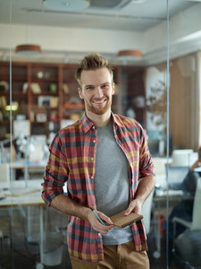 Portrait of cheerful handsome man wearing colorful checkered shirt smiling to camera standing by glass wall in modern office