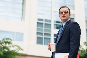 Portrait of confident businessman in sunglasses holding take-out coffee